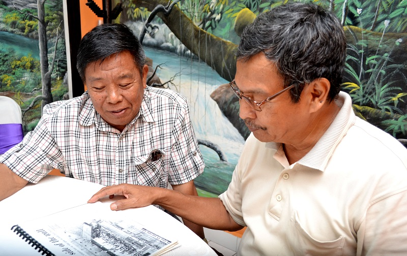 ex-officers Md. Sabri (right) and Zainul reminiscing the days they were working in Pudu Prison, while looking through a newspaper clipping.