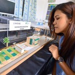 A Laneige team member looking at a model of the rainwater harvesting system.