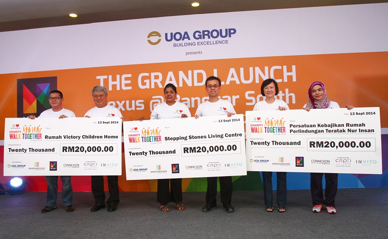 UOA group director Datuk Gan Boon Khuay (second from left), executive director Dr James Tee (fourth from left) and property director CeceliaChan (second from right) presenting mock cheques to representatives of the three homes.