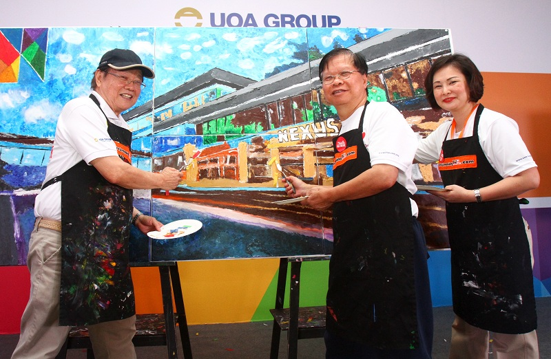 (From left) UOA group chairman Kong Chong Soon, executive director Kong Pak Lim and head of hospitality Anita Khoo putting the finishing touches to the Nexus building artwork.